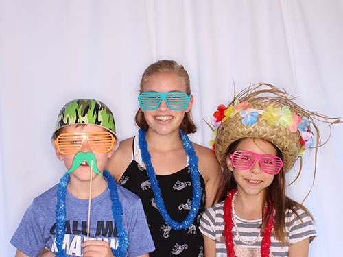 3 children at Stormberg Orthodontics Appreciation Day 2017 smiling with sunglasses and Hawaiian leis