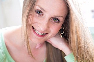 Young Blonde Girl Smiling With Braces & Hand Rested Under Chin